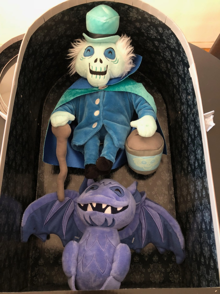 The unboxing process begins for the Haunted Mansion Plush Set, featuring the Hatbox Ghost and Bat